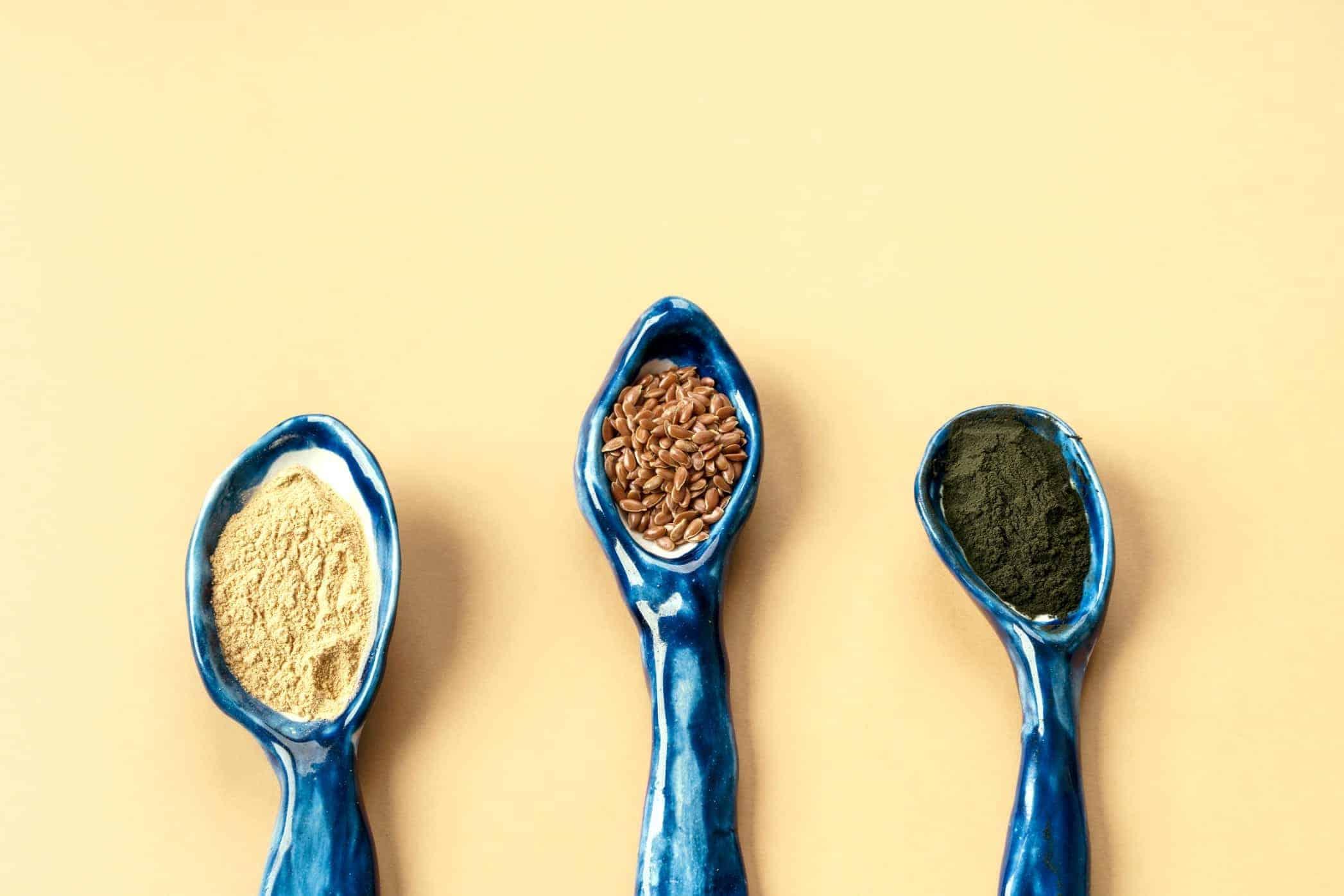 three blue ceramic clay spoons with flax seeds, chlorella powder, matcha and maca